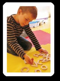 Junge spielt mit Holzbuchstaben